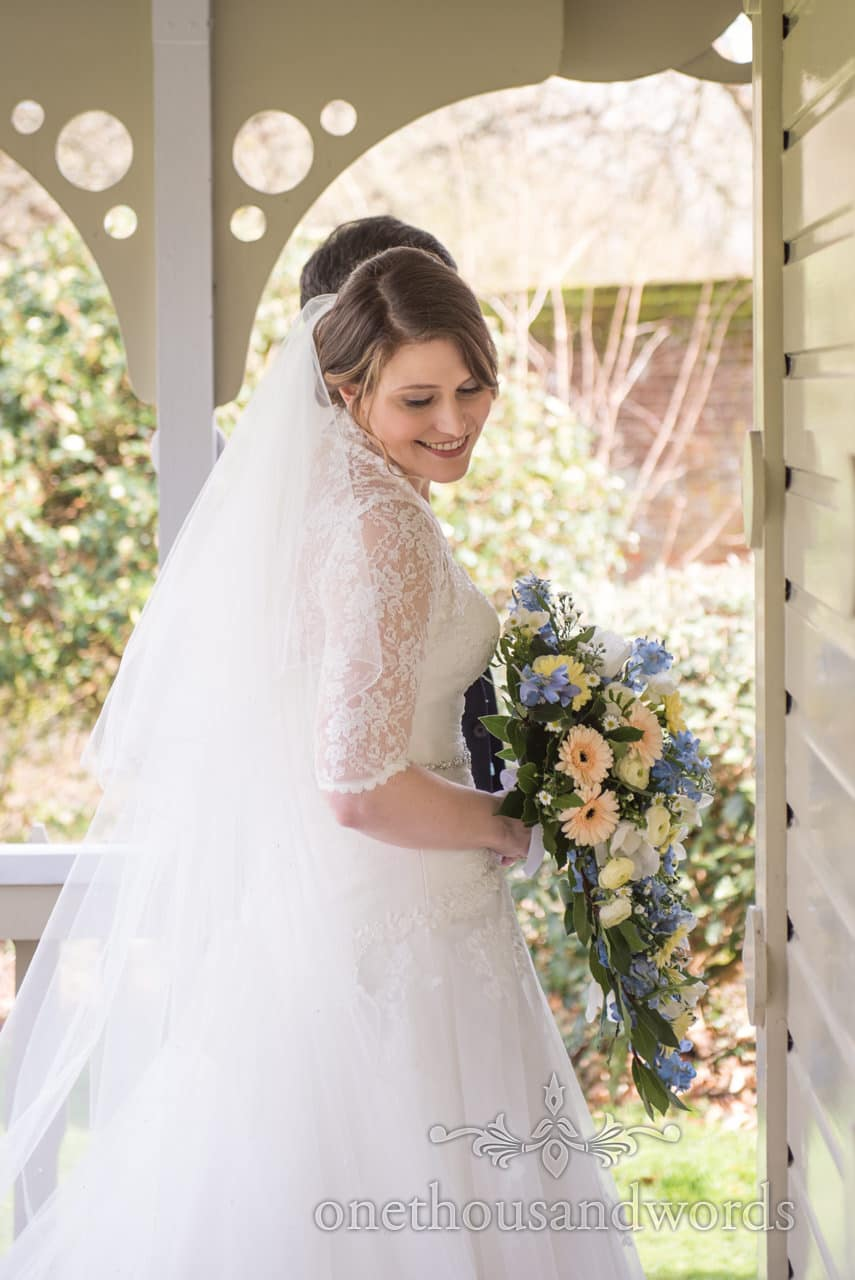 Beautiful bride with soft pastel wedding flower bouquet walks to wedding ceremony