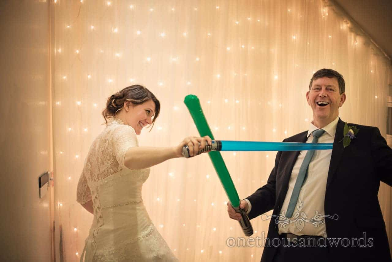 Bride and father of bride play with lightscabers in LED backlit photobooth