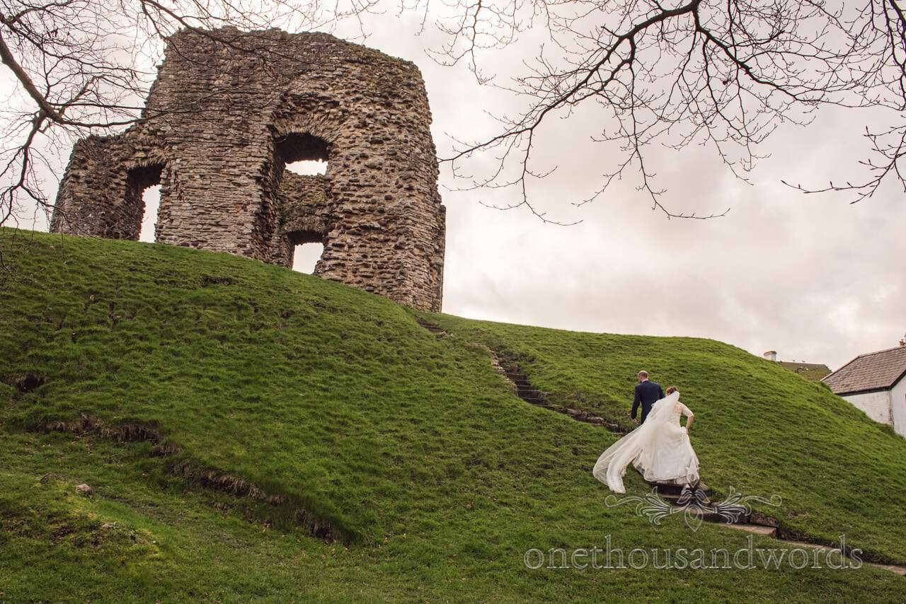 Bride and groom climb hill up to Christchurch Castle ruins at Dorset wedding