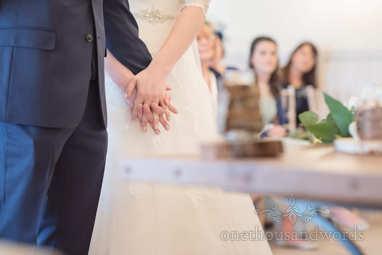 Bride and groom hold hands during wedding ceremony in Christchurch, Dorset
