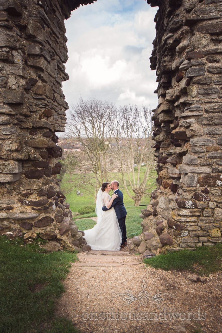 Bride and groom kiss between the walls of ruins of Christchuch Castle in Dorset