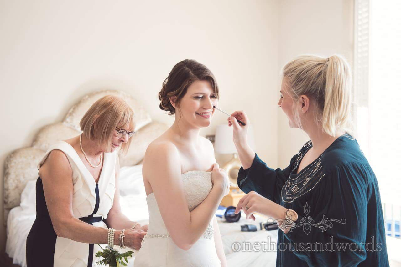 Bride has wedding make-up styled whilst being laced into wedding dress