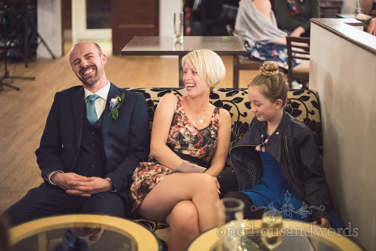 Documentary wedding photograph of groom laughing with guests at Kings Arms Hotel