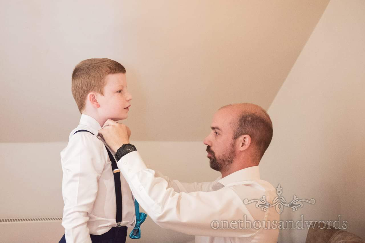 Groom helps his son put on bow tie on wedding mornging at Kings Arms Dorset