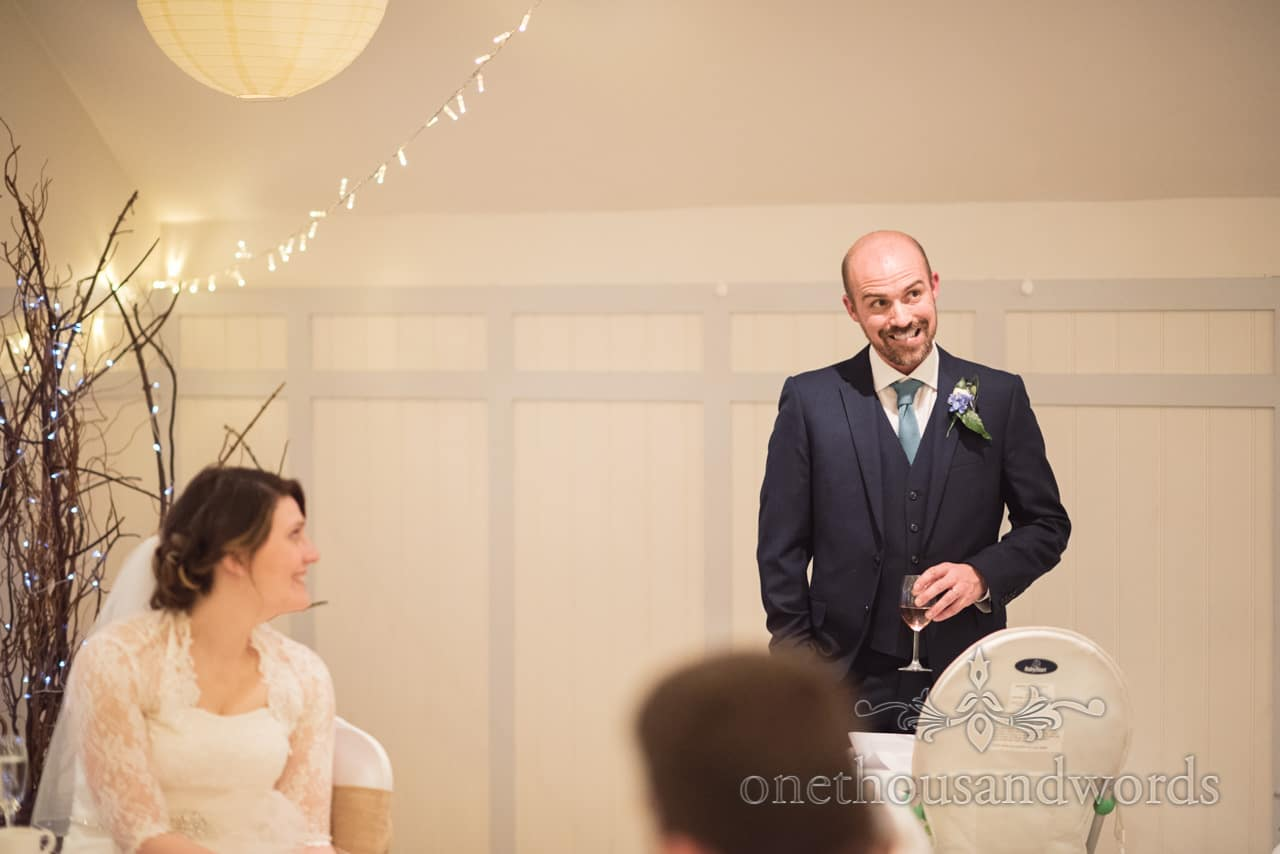 Groom pulls a face whilst making grooms weddign speech in Christchurch, Dorset