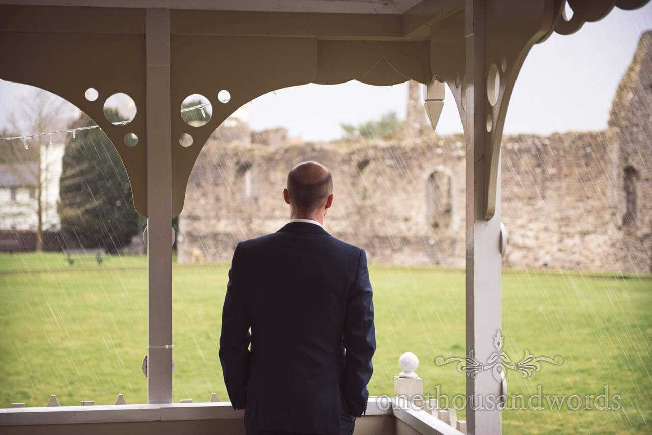 Groom watches rain at Kings Pavillion wedding in Christchurch, Dorset