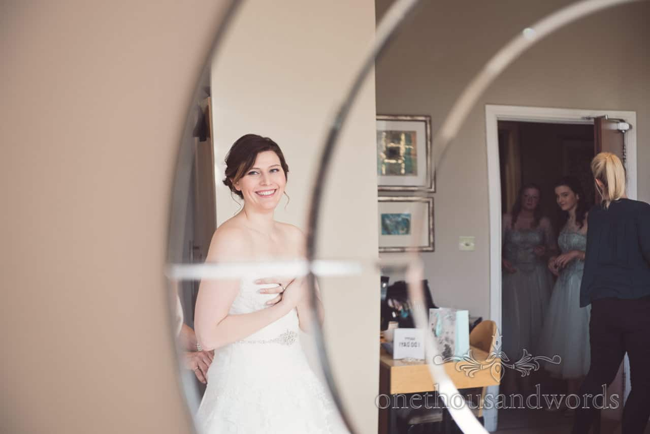 Happy bride is laced into her wedding dress reflection in mirror at Kings Arms Hotel