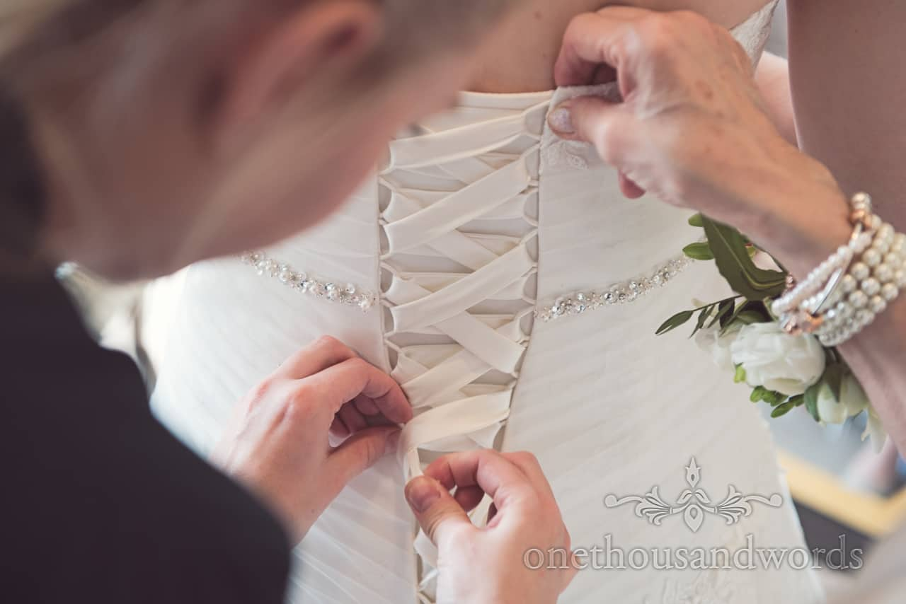 Lacing the back of a wedding dress with diamonte applique