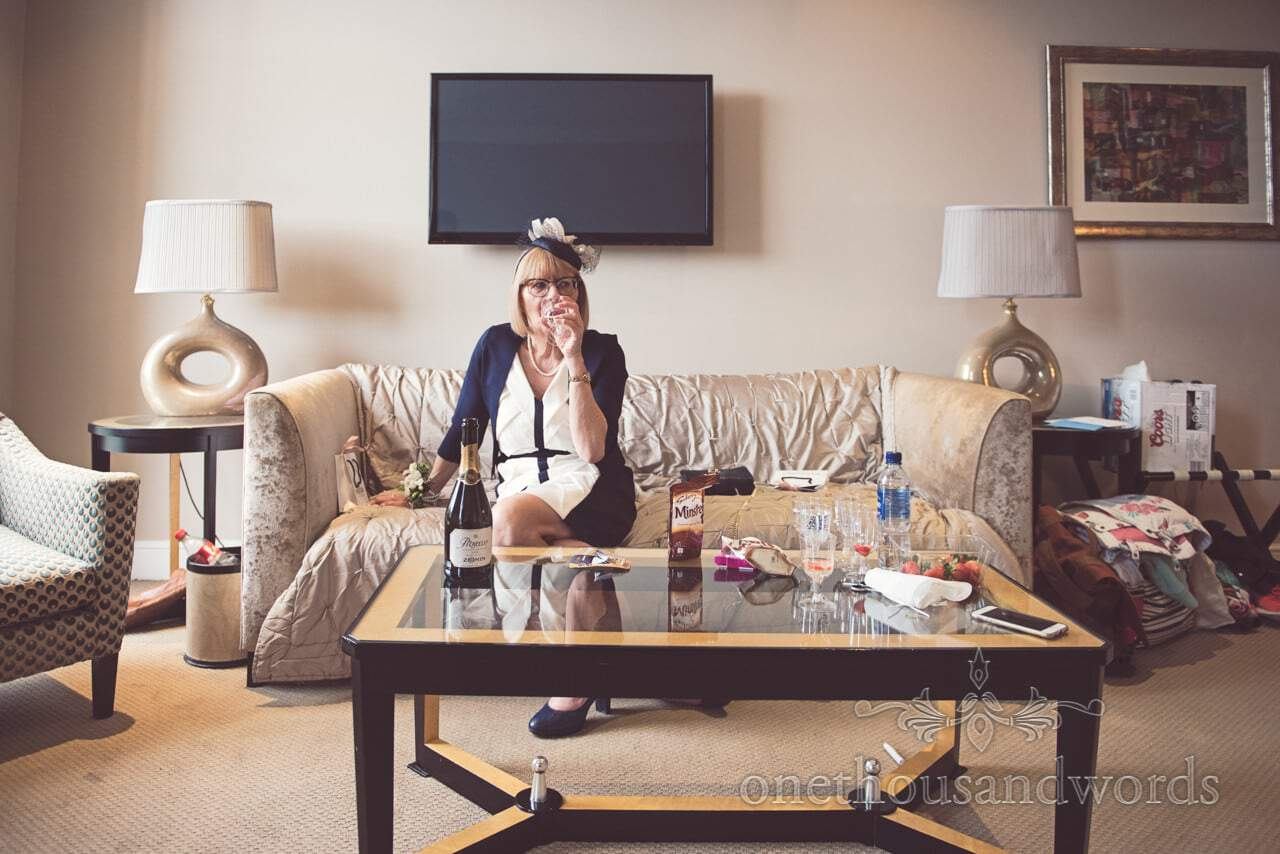 Mother of the bride enjoys a glass of Prosecco during bridal preparation