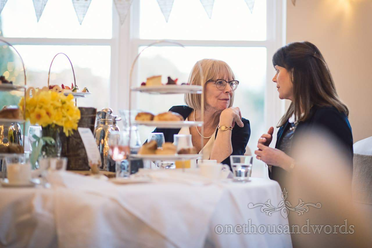 Mother of the bride enjoys chat during high tea wedding breakfast