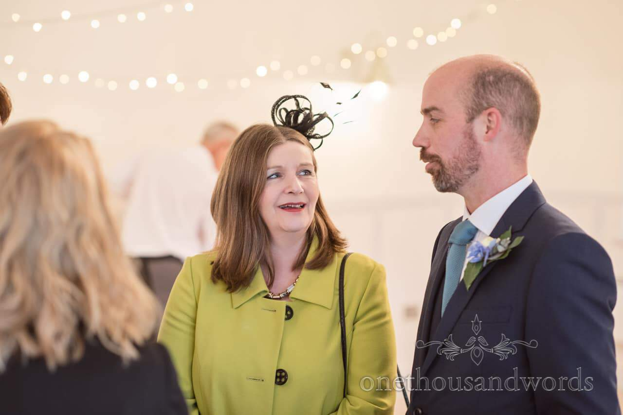 Mother of the groom shares a joke wearing black fascinator and lime green coat