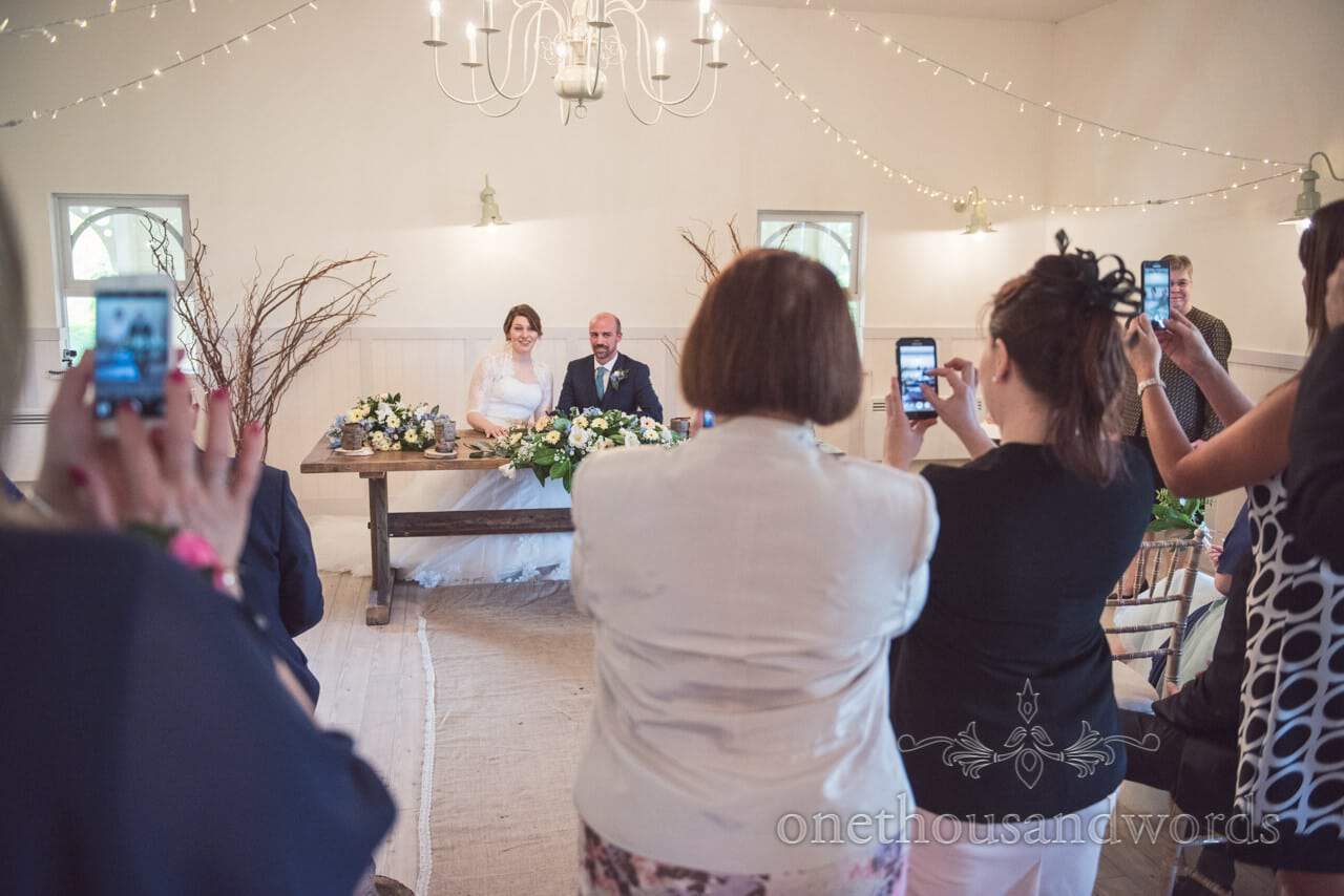 Phone cameras at Kings Pavillion wedding ceremony in Christchurch Dorset