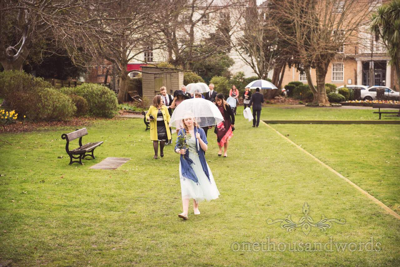 Wedding guests arrive under umbrellas at rainy wedding in Dorset