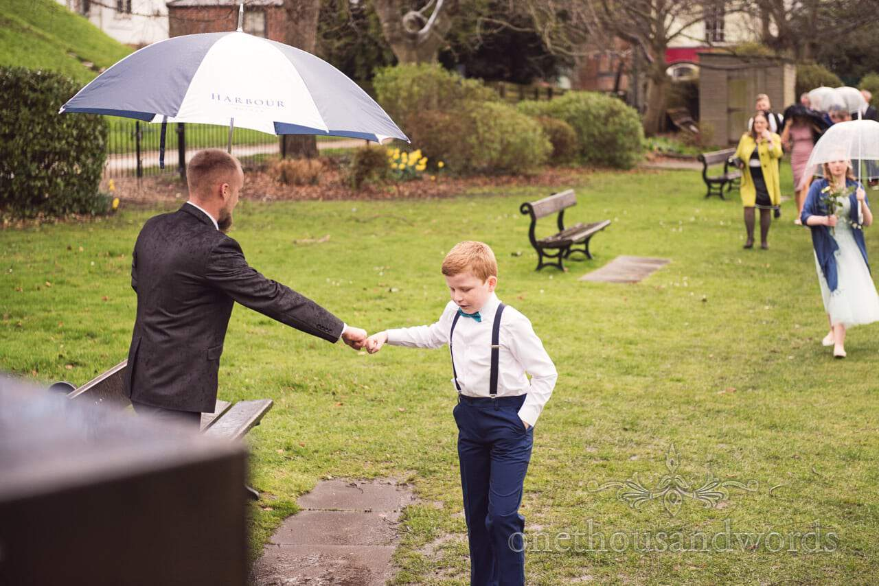 Wedding guests fist bump as the rain comes down at Christchurch wedding