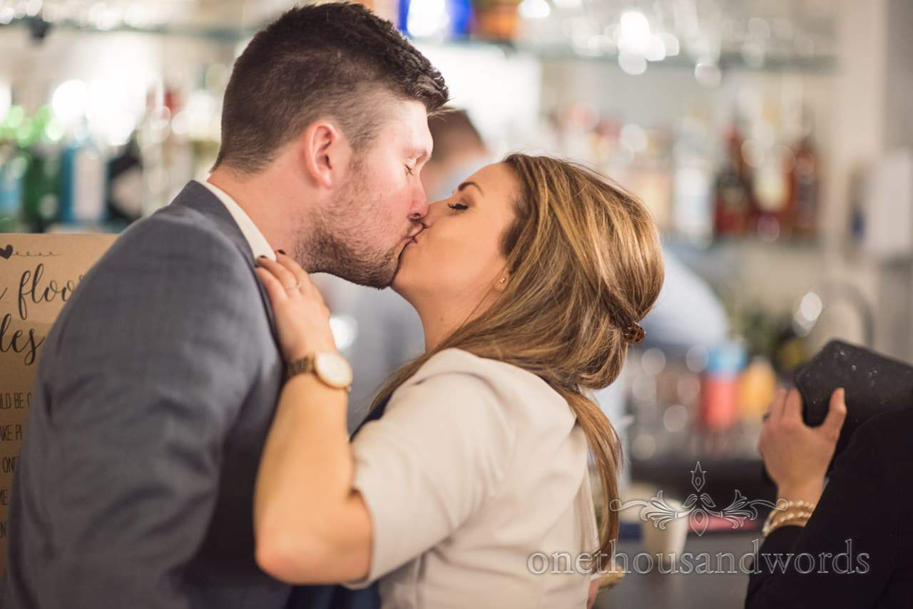 Wedding guests sneak a kiss at the bar at Kings Arms Christchurch Wedding