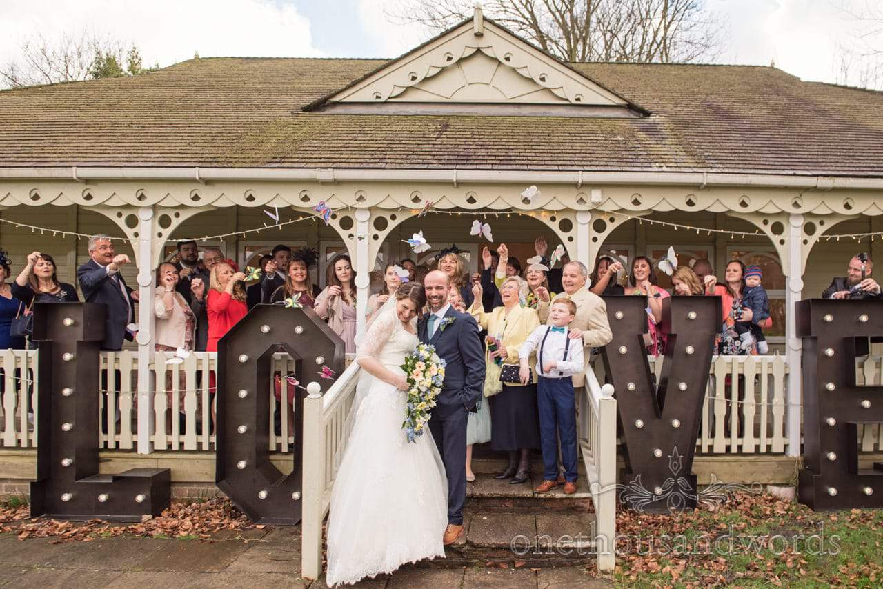 Wedding guests throw butterfly confetti at bride and groom outside Kings Pavillion