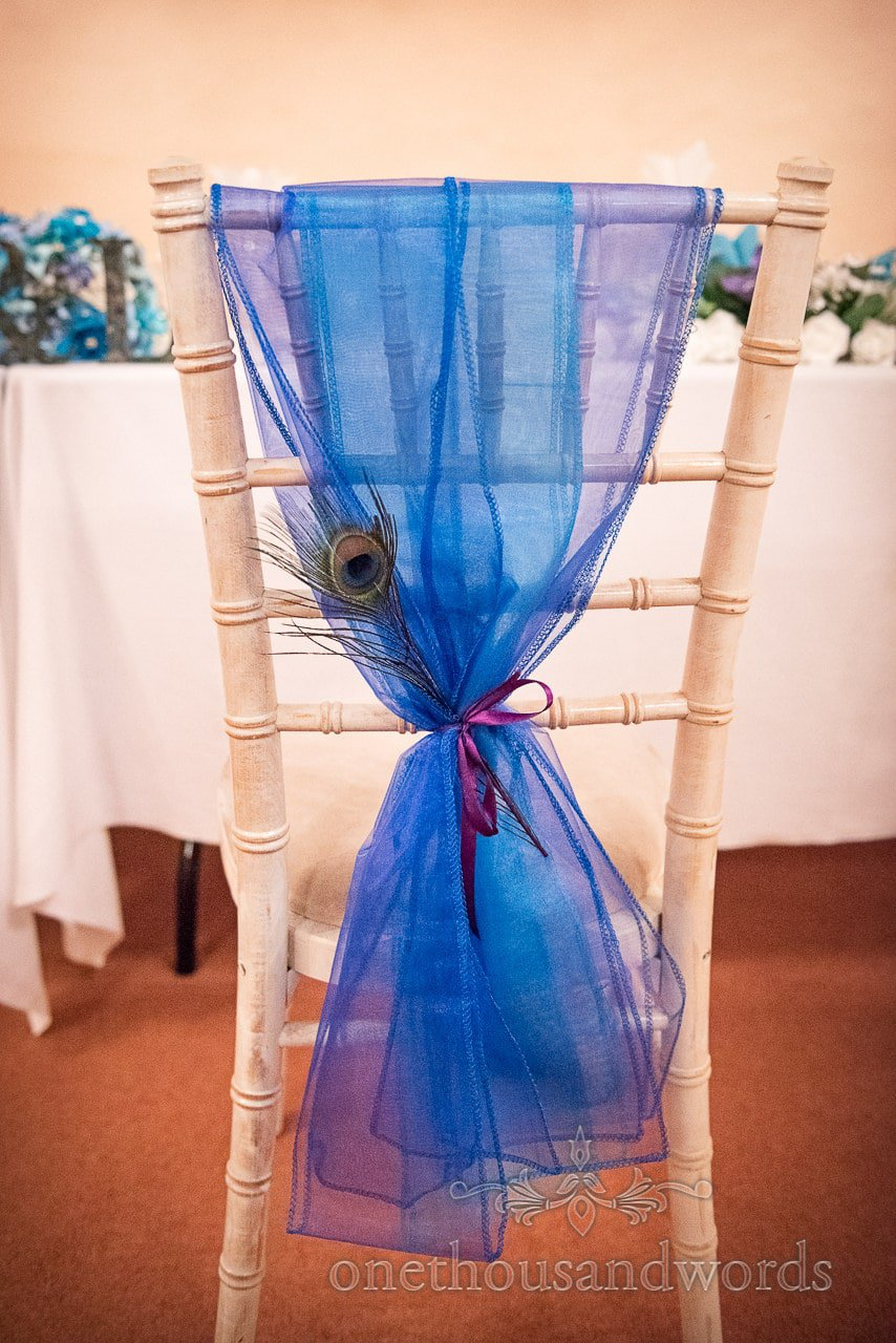 Blue wedding chair sash with peacock feather on distressed rustic wedding chair