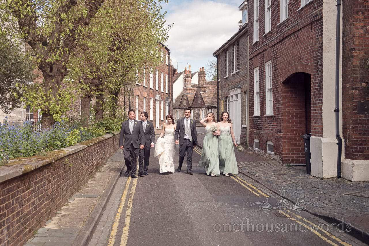 Bridal party walk down the street at Scaplens Court wedding photographs
