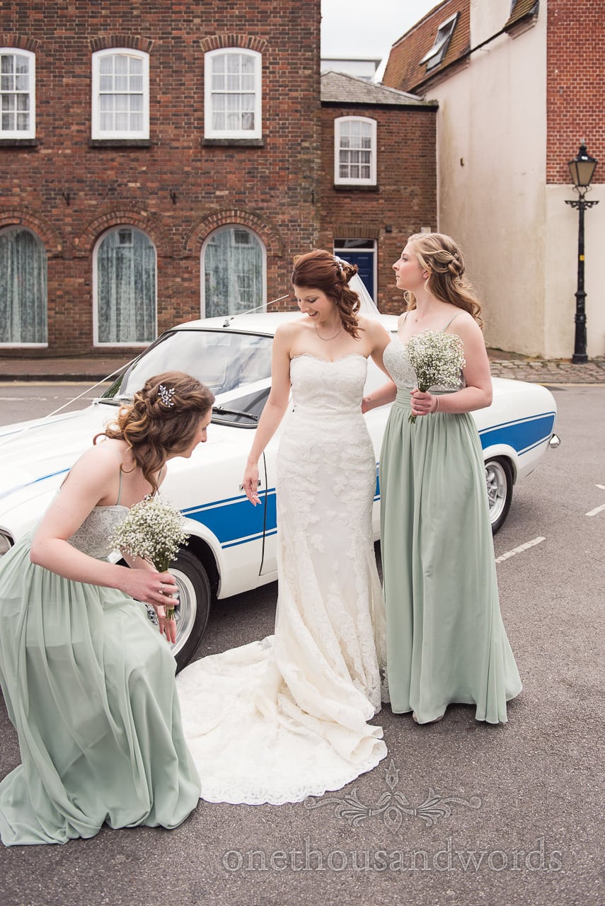 Bride and bridesmaid with wedding car at Scaplens Court wedding photographs
