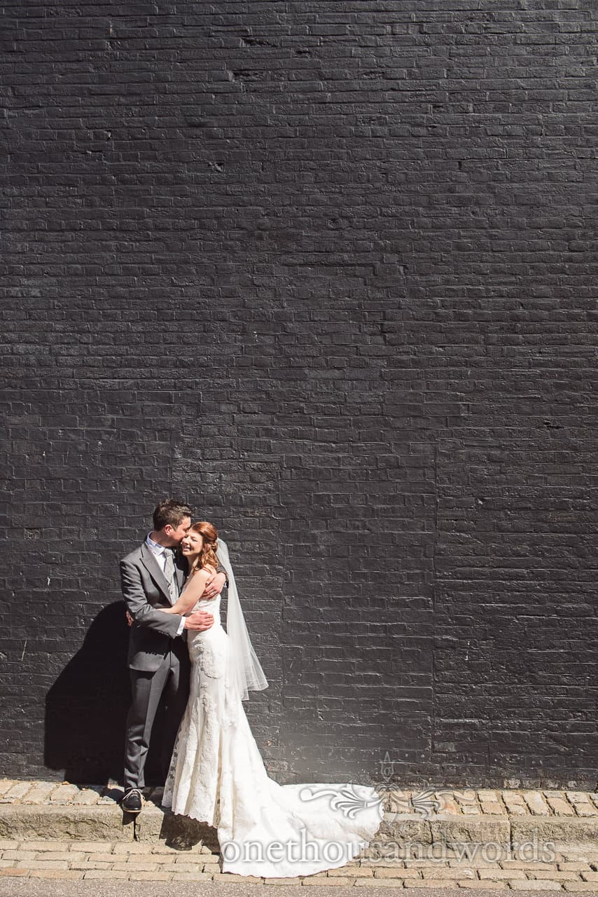 Bride and groom against painted brick wall at Scaplens Court wedding photographs