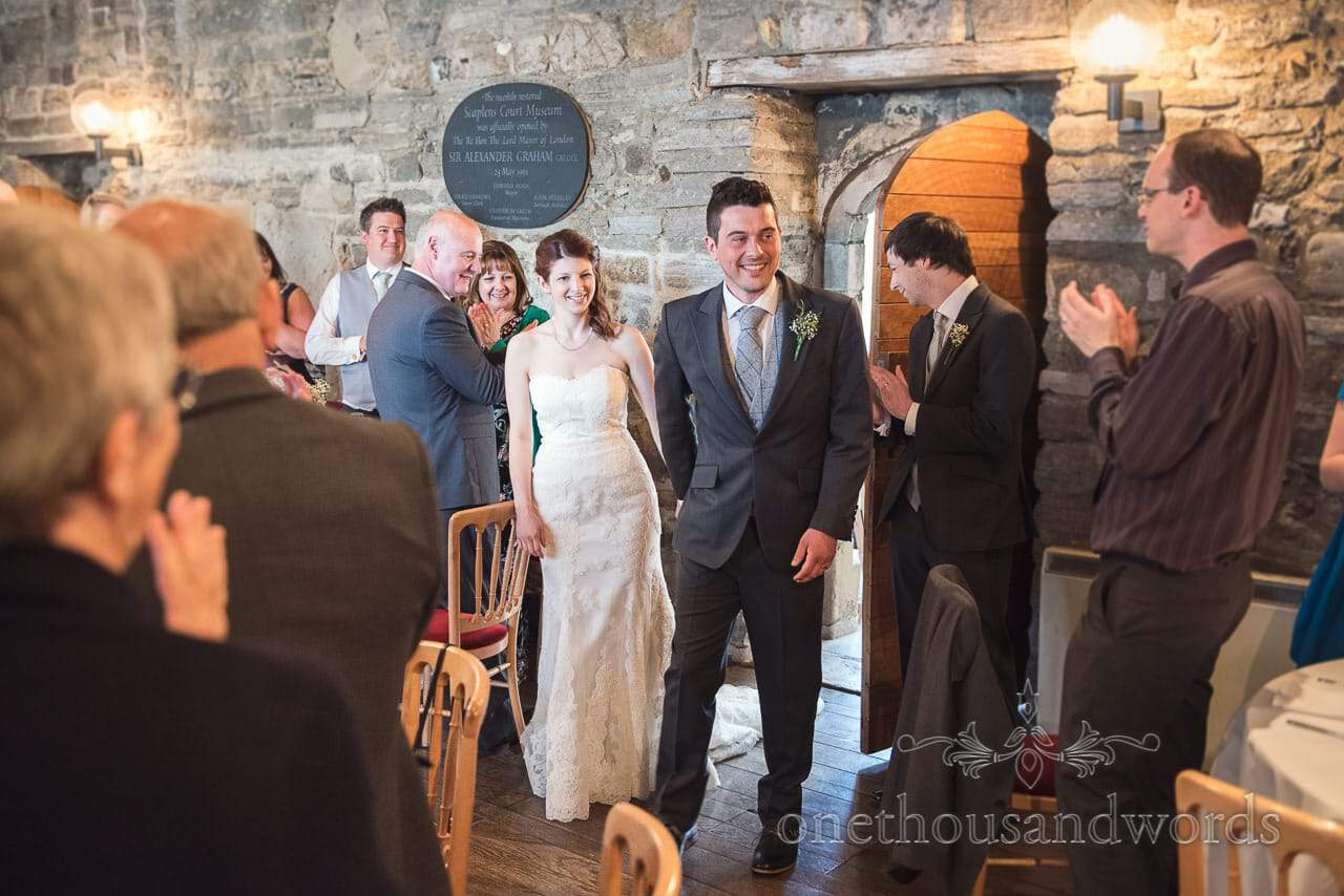 Bride and groom are welcomed into room at Scaplens court wedding photographs