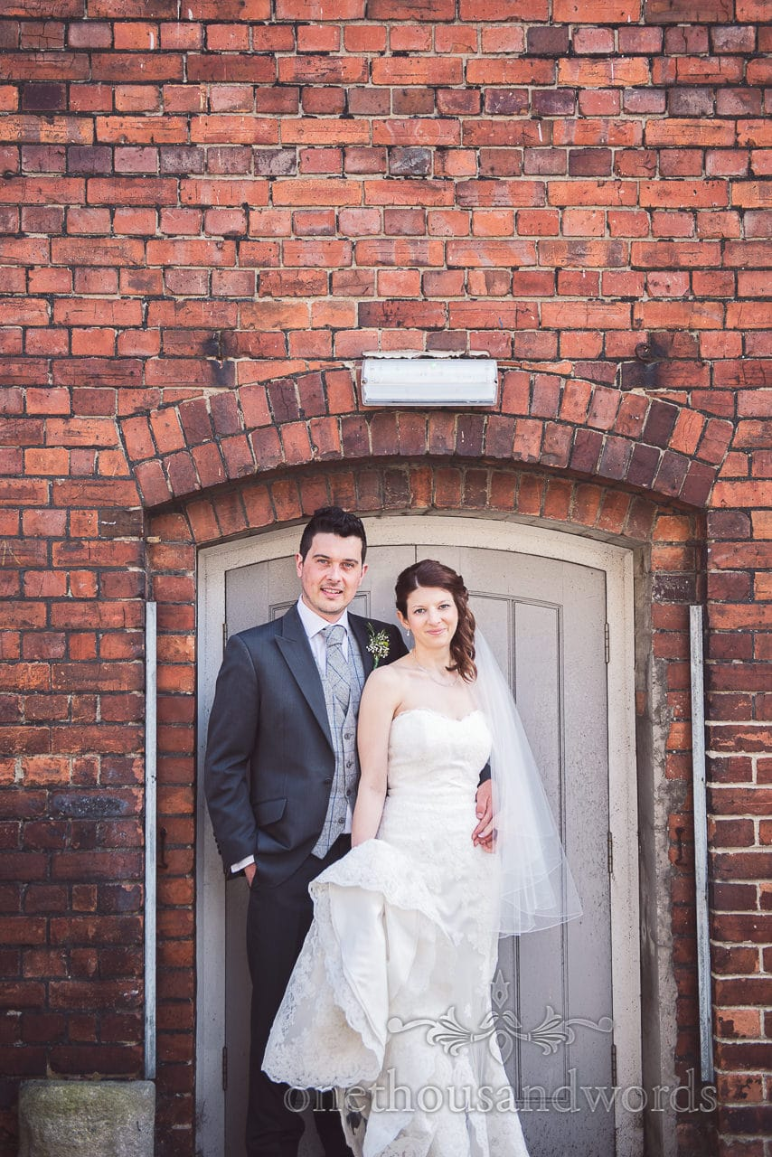 Bride and groom in brick doorway at Scaplens Court wedding photographs