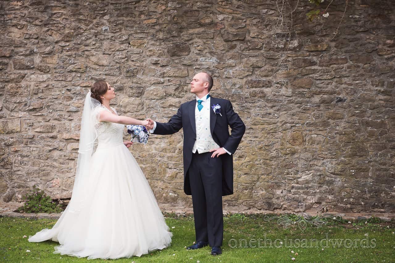 Bride and groom shaking hands at Walton Castle wedding photographs