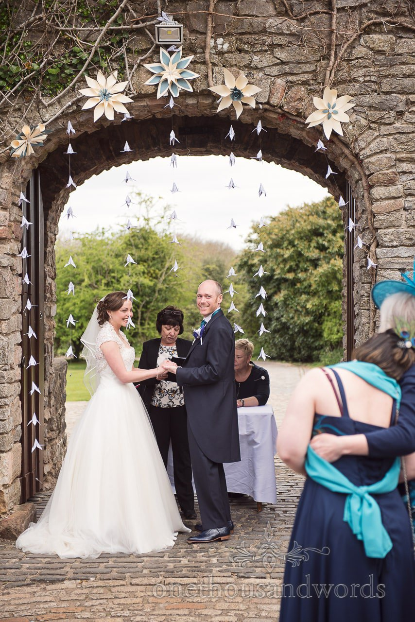 Bride and groom under decorated archway at Walton Castle wedding photographs