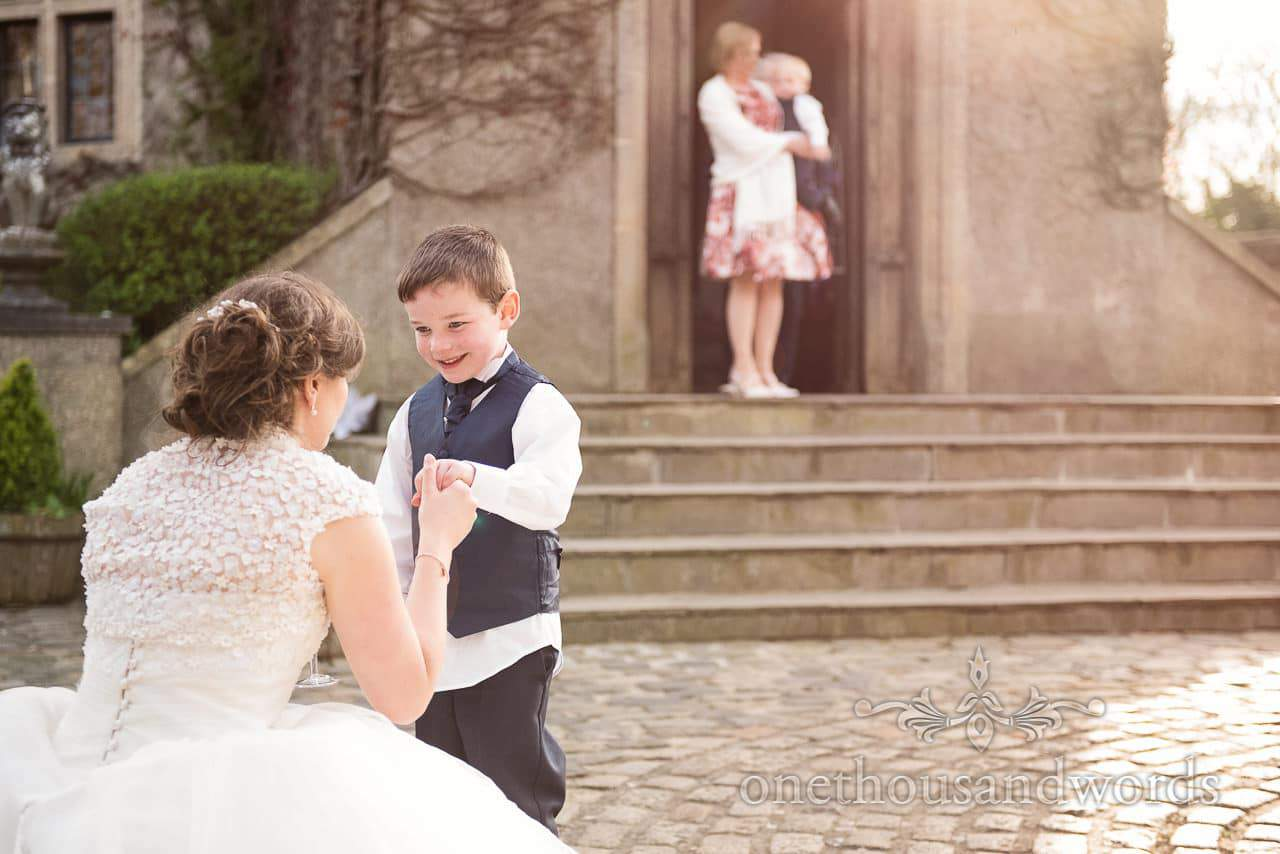 Bride and page boy in courtyard at Walton Castle wedding photographs