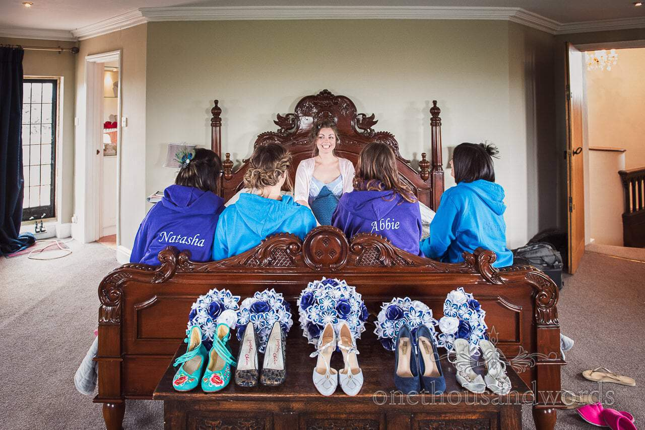 Bride, bridesmaids, wedding shoes and paper wedding bouquets on ornate wooden bed at Walton Castle
