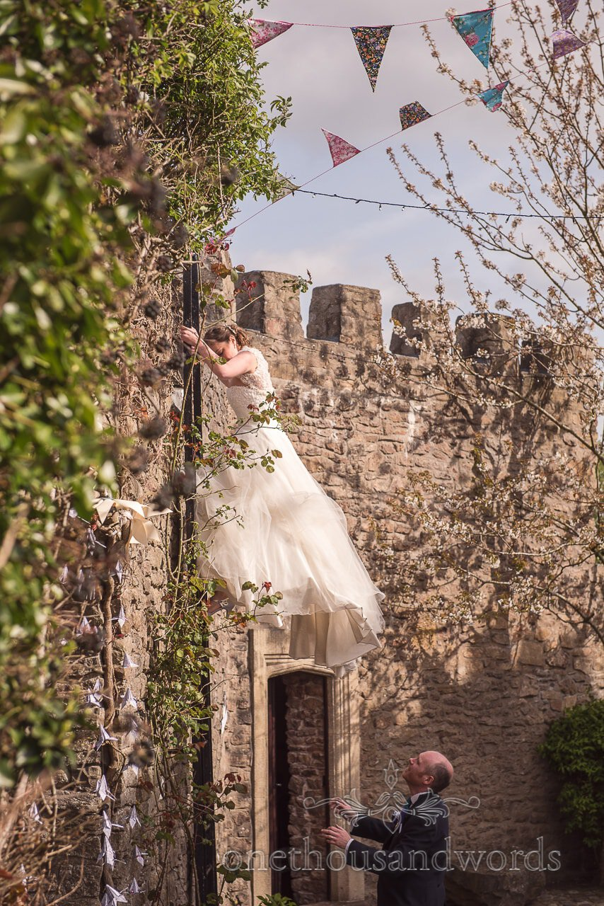 Bride climbs wall ladder at Walton Castle wedding photographs