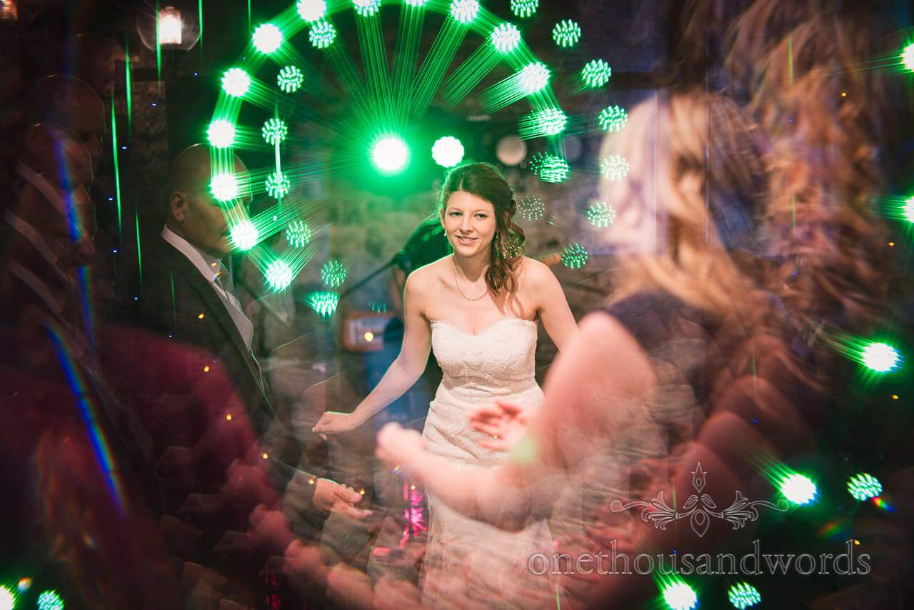 Bride dancing in the lights at Scaplens court wedding photographs