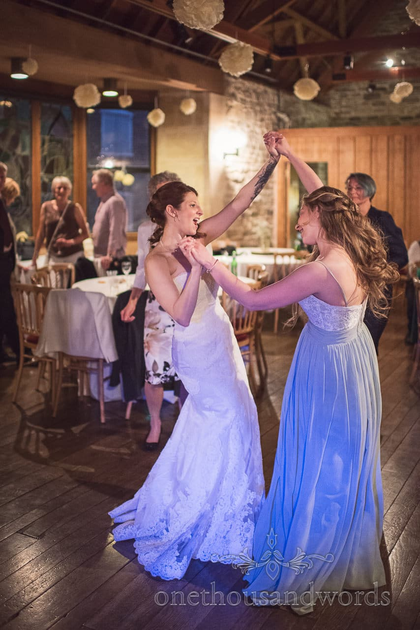 Bride dancing with bridesmaid at Scaplens court wedding photographs