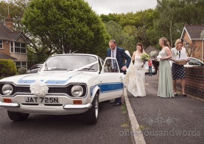 Bride gets into Ford Escort wedding car at Scaplens Court wedding photographs
