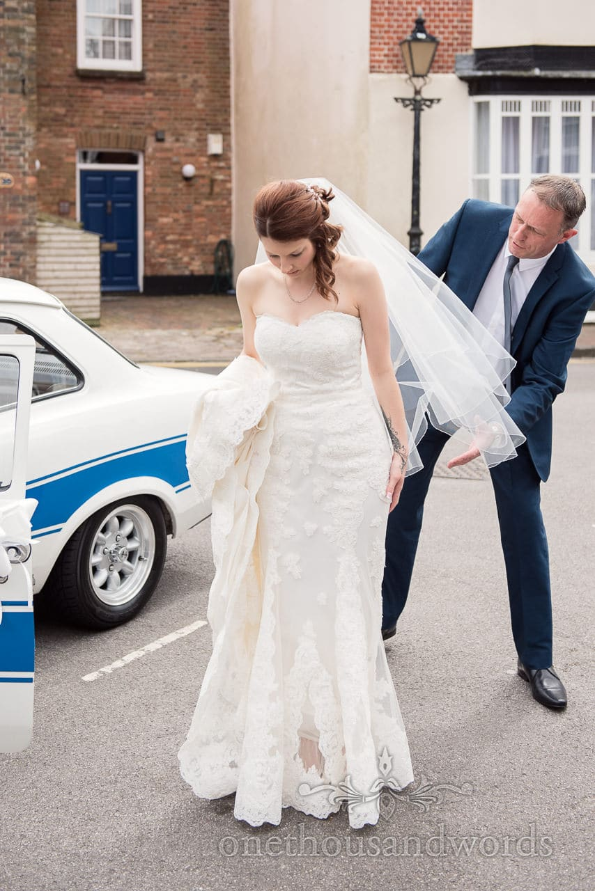 Bride helped with her dress at Scaplens Court wedding photographs