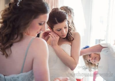 Bride puts in ear rings on morning of Scaplens Court wedding photographs