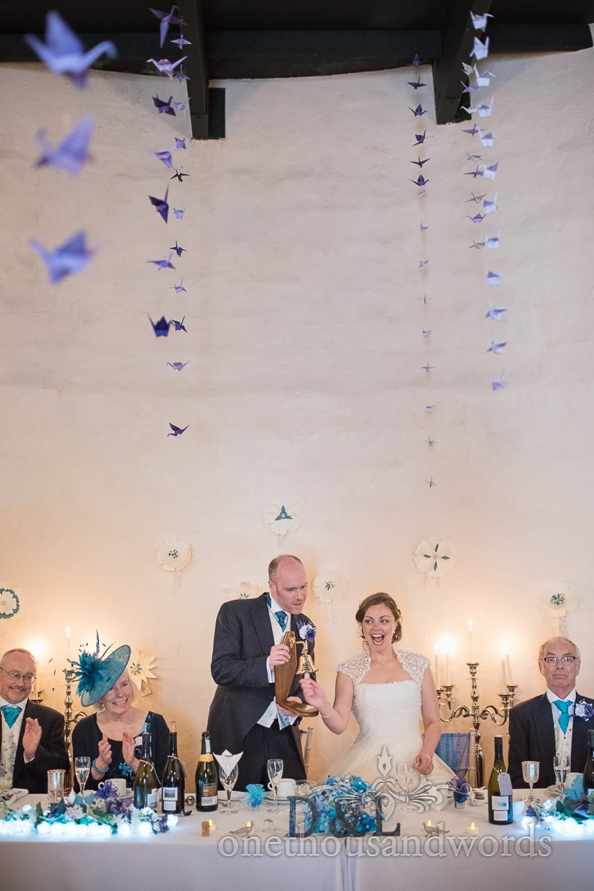 Bride rings the bell at wedding breakfast from Walton Castle wedding photographs