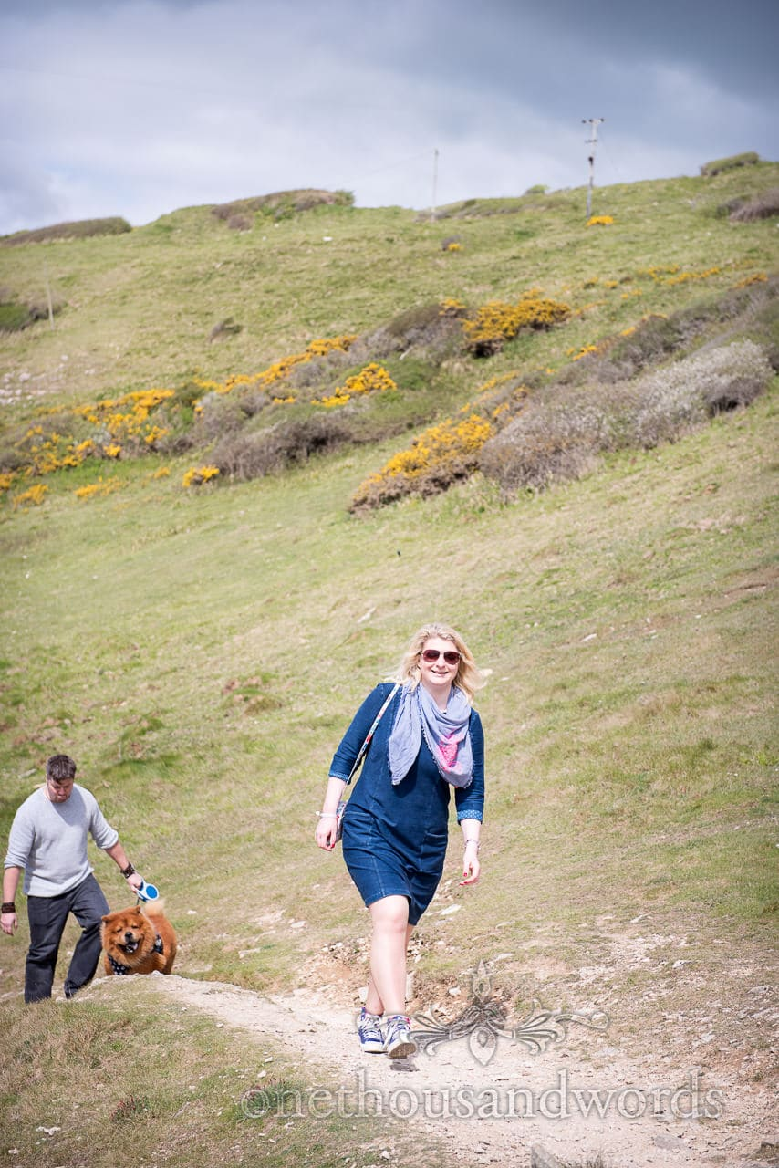 Bride to be walking on coastal path at Dorset engagement photo shoot with husband to be and dog