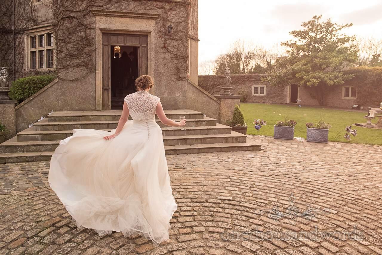 Bride walks across courtyard at Walton Castle wedding photographs
