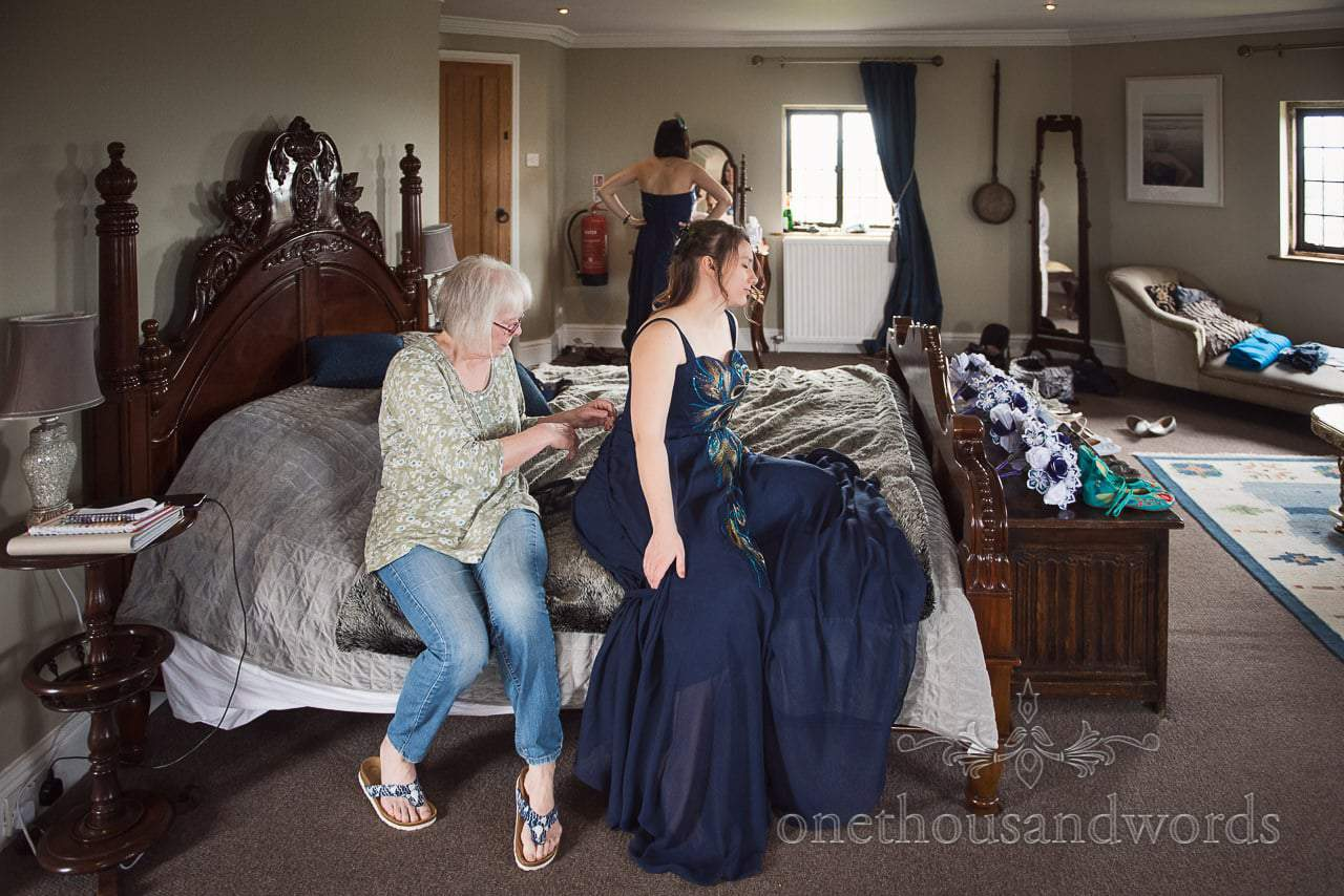 Bridesmaid is laced into deep blue peacock pattern bridesmaids dress in Walton Castle