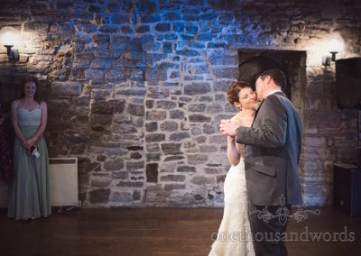 Bridesmaid looks on at first dance from Scaplens court wedding photographs