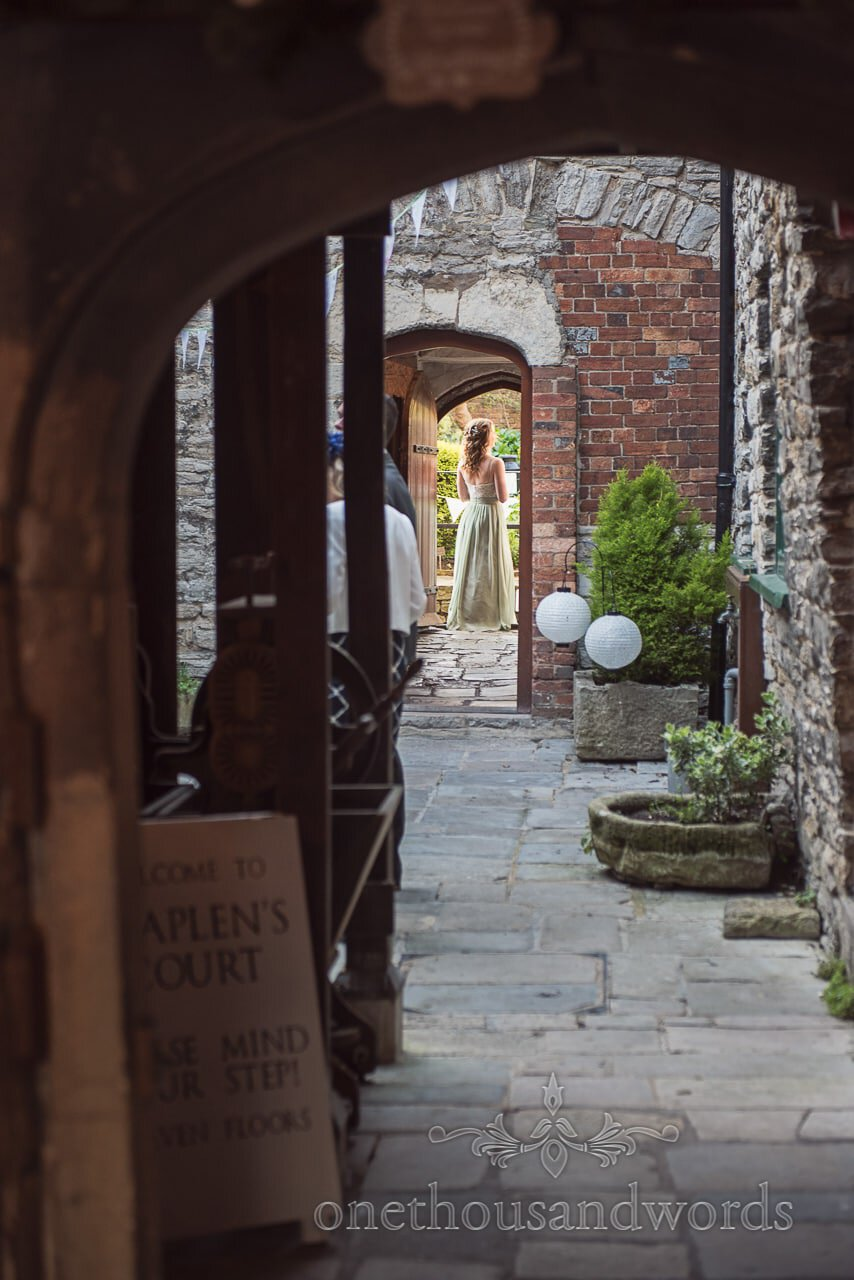 Bridesmaid through the doorway at Scaplens court wedding photographs