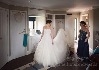 Bridesmaids help bride with dress at Walton Castle wedding photographs