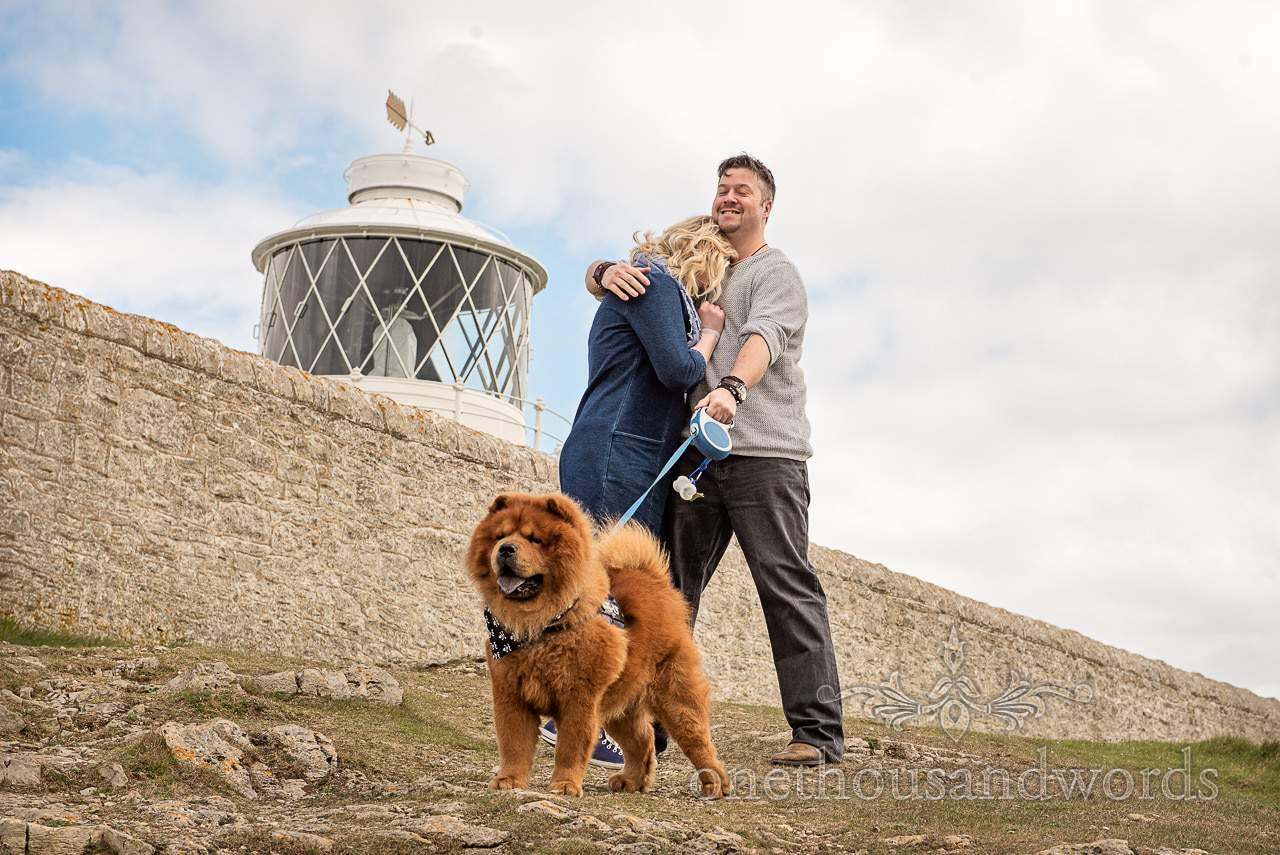 Bride to be hides face in husband to be's chest with chow chow dog and lighthouse at Durslton engagement photo shoot