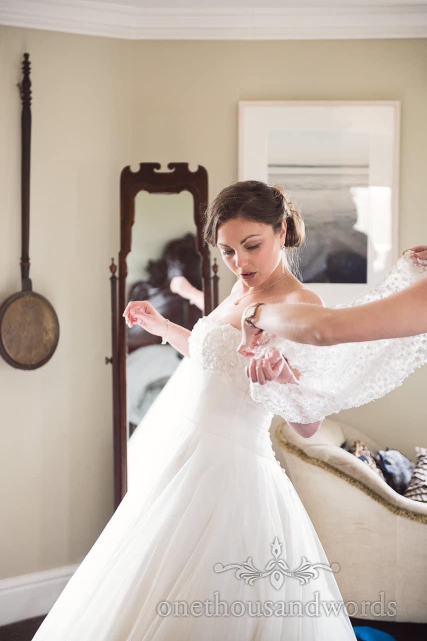 Documentary wedding photo of bride putting on bolero on wedding morning
