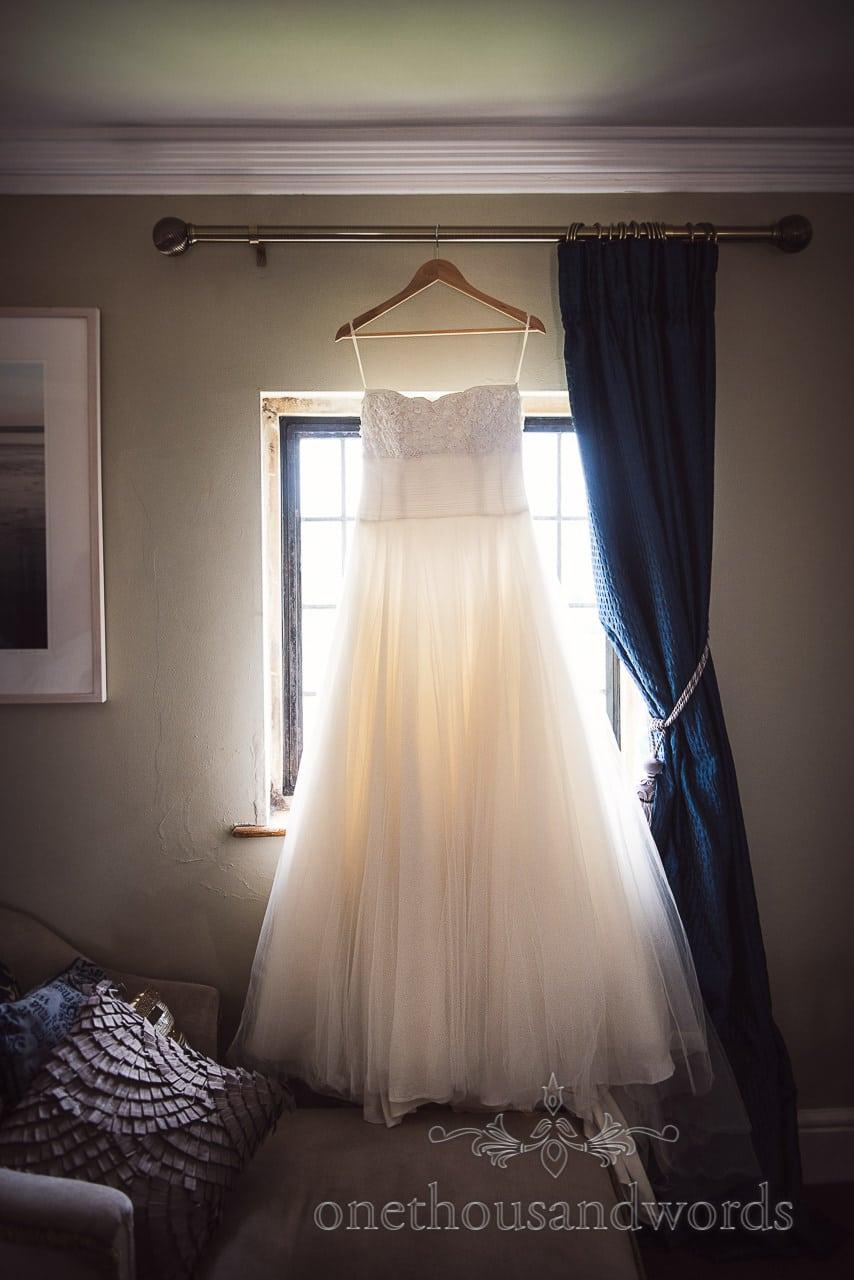 Dress hangs in window at Walton Castle wedding photographs