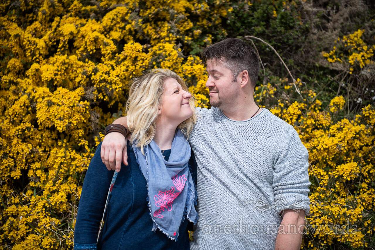 Durlston Country Park Engagement Photos couple pull funny faces at each other in front of yellow gorse flowers