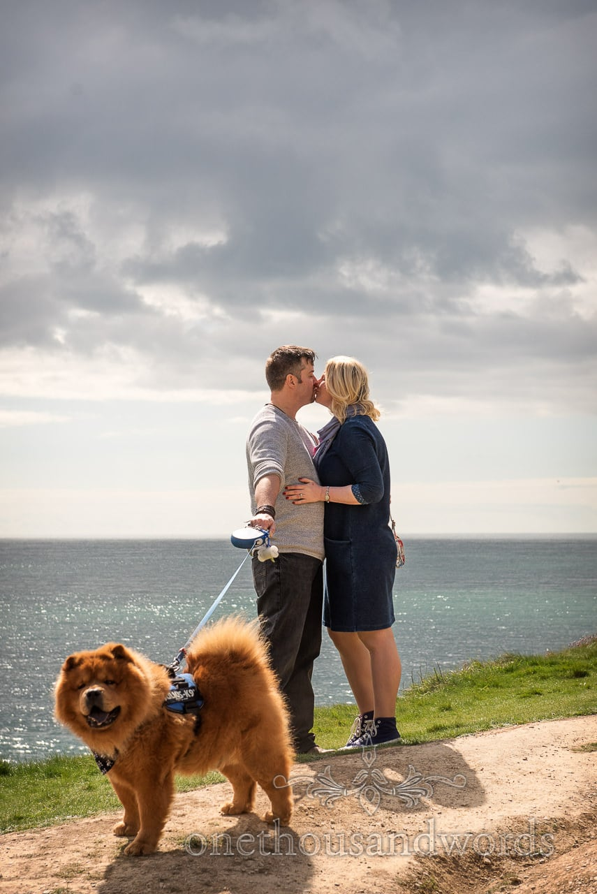 Engagement photo shoot couple kiss by the sea with dog