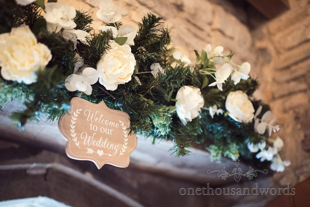 Floral wedding welcome over doorway at Scaplens court wedding photographs