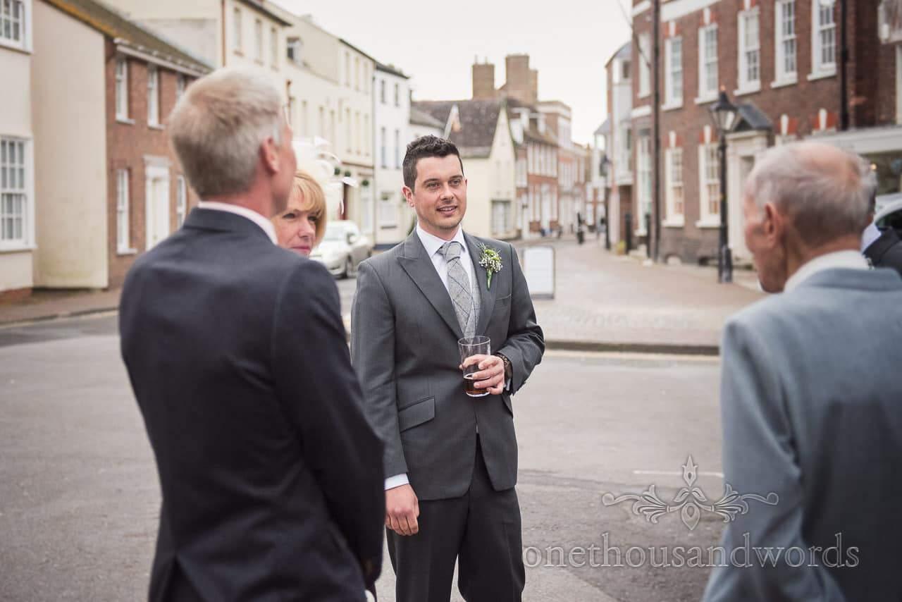 Groom enjoys a pint before Scaplens Court wedding photographs